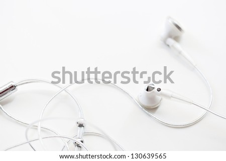 Close up detail view of a pair of musical earphones laying together with cable around them, isolated on a white background. - stock photo