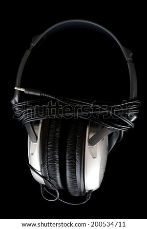 Close up detail view of a pair of professional dj headphones against a black background with the cable wrapped around it. Musical equipment still life and isolated objects. - stock photo