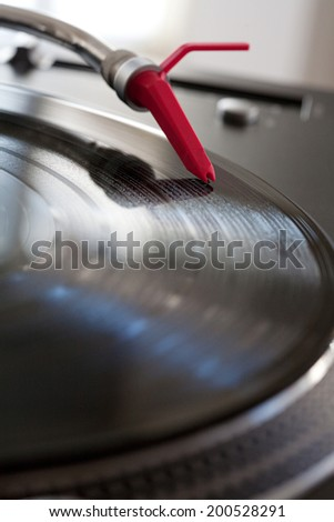 Close up detail view of a record player with a red needle touching the groove of a vinyl album playing music, interior. Still life professional musical equipment objects.