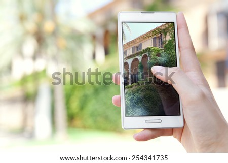 Close up detail view of a tourist woman hands holding a touch screen smartphone mobile cell device, to take holiday pictures of a building on vacation. Travel and lifestyle technology outdoors. - stock photo