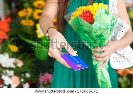 Close up detail view of a woman customer offering her credit card for payment and holding it in her hand while purchasing a colorful bouquet of flowers in a market stall florist shop, outdoors. - stock photo