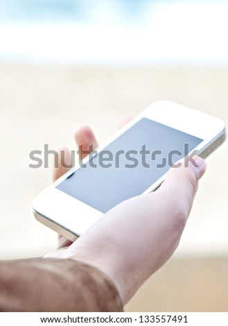 Close up detail view of a woman's hand holding a modern smart phone with a blank screen against a neutral background and the sea. - stock photo