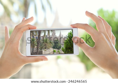 Close up detail view of a young tourist woman hands holding a smartphone mobile cell device, taking pictures of a monument while sightseeing on a holiday trip. Travel and technology outdoors. - stock photo