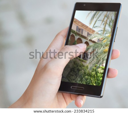 Close up detail view of a young woman hand holding a smart phone with touch screen and taking pictures of sights and monuments while visiting a destination city on a summer holiday break. - stock photo