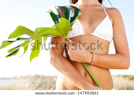 Close up detail view of a young woman middle body section wearing a bikini on a beach and holding a large exotic green leave in her hand, feeling healthy and beautiful. Blue sky. - stock photo
