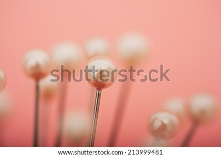 Close up detail view of multiple sewing pins and needles standing against a pink background in a dressmaking fashion interior. Still life of shining sewing pins heads. - stock photo