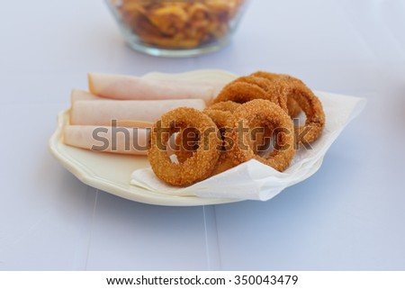 Close up detailed front view of a plate of fried onion rings with jambon served on a plate. - stock photo