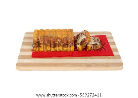 Close up detailed side view of baton cacao cake sliced on a cutting board, isolated on white background.