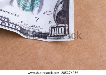 Close up detailed top view of crumpled one hundred dollar banknotes, on brown background. - stock photo