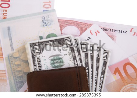 Close up detailed top view of heap of dollar and euro banknotes under a leather man wallet, isolated on white background. - stock photo