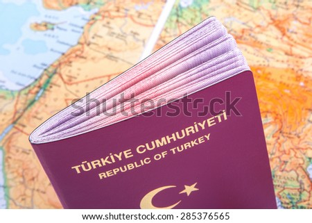 Close up detailed view of a Turkish passport standing on a world map. - stock photo