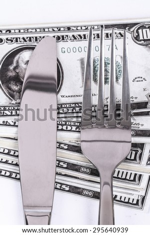 Close up detailed view of one hundred dollar banknotes under a steel fork and knife, isolated on white background. - stock photo