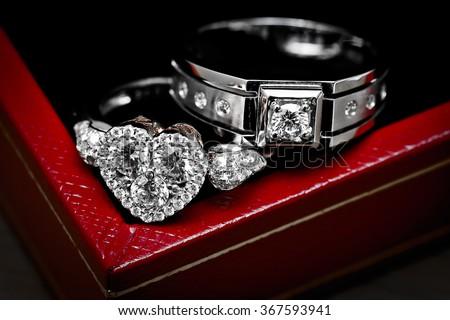 Close up diamond couple wedding rings on luxury red box - stock photo