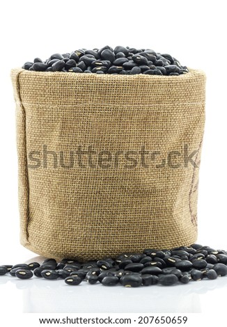 Close up dried black beans in Sacks fodder on white background