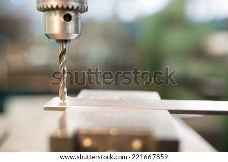 Close up drill tool in chuck during metal cutting process hole boring in iron piece at industrial factory workshop  - stock photo
