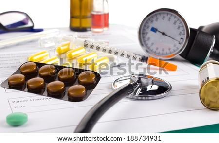 close-up drugs and stethoscope on medical authorization form  on white background - stock photo