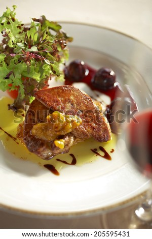 close up duck liver grilled and cherry sauce in white dish
