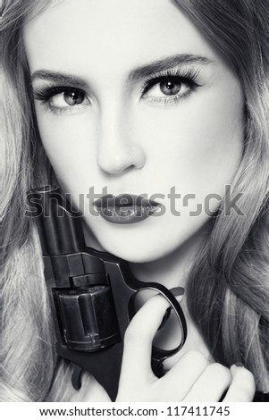 Close-up duotone portrait of young beautiful woman with revolver in her hand - stock photo