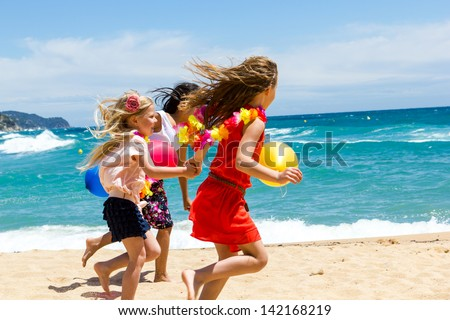 Close up dynamic shot of youngsters running on beach. - stock photo