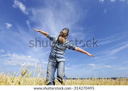 close-up eccentric aviator man, arms outstretched in a wheat field against a blue sky - stock photo
