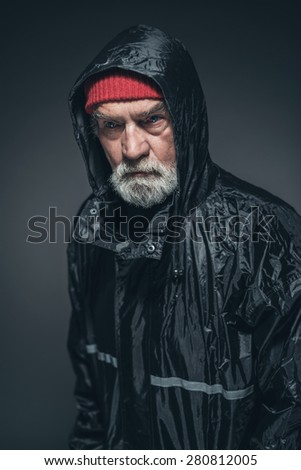Close up Elderly Man with White Facial Hair, Wearing Red Bonnet and Black Rain Slicker, Looking Straight at the Camera. Captured in Studio with Black Background. - stock photo
