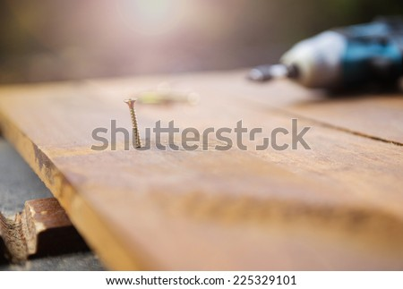 Close up electric drill and nail left on wooden floor - stock photo