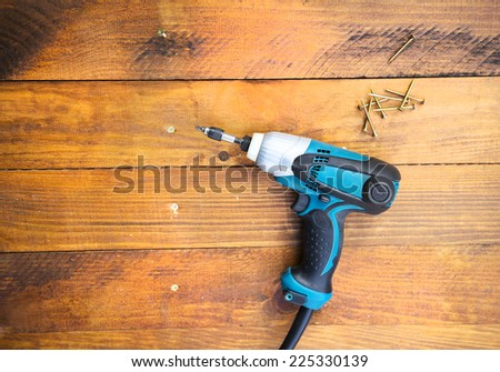 Close up electric drill and nails left on wooden floor - stock photo