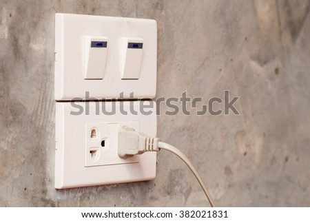 Close up electric plug and switch on grey wall, background - stock photo