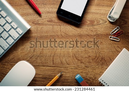Close up Electronic Devices and School Supplies on Wooden Table, Resting on the Edges, with Central Copy Space for Texts. - stock photo