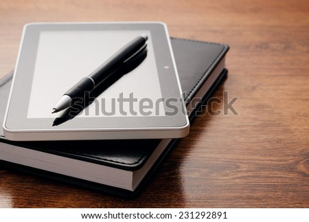 Close up Electronic Tablet Device on Notebook Resting on Wooden Table. Emphasizing Learning Concept.
