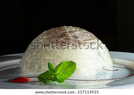 close-up elegant dessert flamb���© cheesecake on a white plate decorated with mint leaves and jam - stock photo