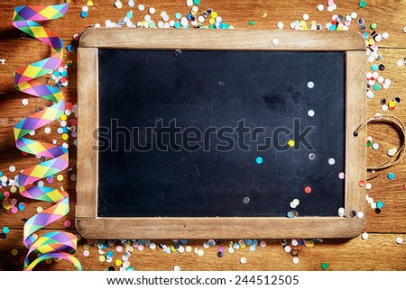 Close up Empty Black Board on Wooden Table with Colorful Streamers and Confetti. Emphasizing Copy Space. - stock photo