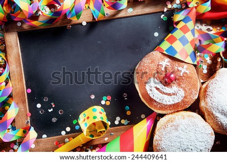 Close up Empty Black Board with Decorated Carnival Donuts and Festival Props. Emphasizing Copy Space at the Center for Texts. - stock photo