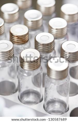 Close-up empty laboratory glass flasks in medicine cartridge. Shallow DOF - stock photo