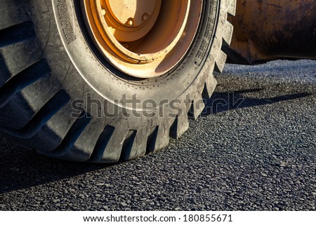 Close-up excavator tire in the road - stock photo