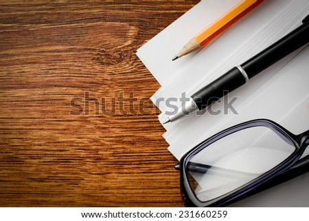 Close up Eyeglasses and Office Supplies like Pen, Pencil and Paper on Top of Wooden Table with Copy Space on the Left Side. - stock photo