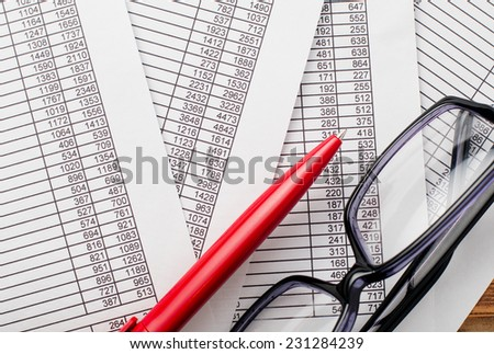 Close up Eyeglasses and Red Ballpoint Pen on Top of Business Documents with Number Prints. - stock photo