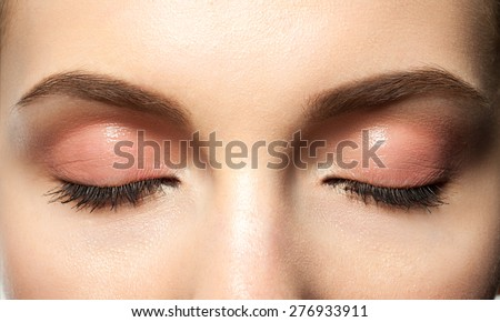 Close-up eyes closed with makeup with brown eyebrows and black lashes - stock photo