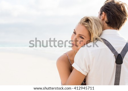 Close up face of a young woman embracing her boyfriend at beach. Couple having a romantic time at beach. Woman leaning her face on the shoulder of her boyfriend, copy space on left. - stock photo