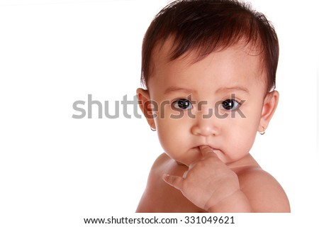 Close up face of adorable baby girl chewing her finger and looking at camera with innocent expression, isolated on white background - stock photo