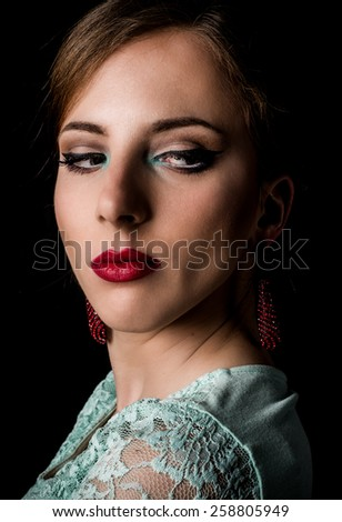 Close up Face of an Elegant Young Woman with Make up Staring to the Bottom Right of the Frame on a Black Background. - stock photo