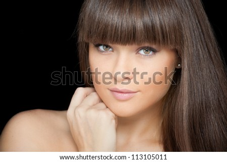 Close-up face of beautiful young woman on black background - stock photo