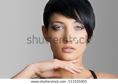Close-up face of beautiful young woman on gray background - stock photo