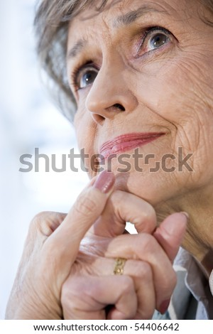 Close up face of senior woman thinking, hands on chin - stock photo