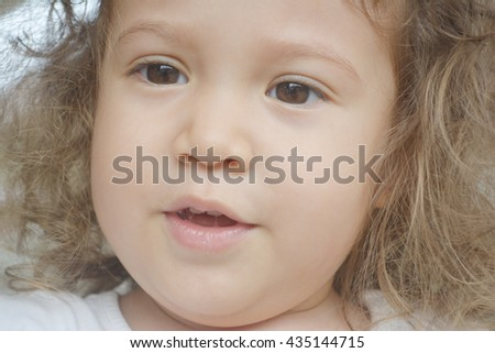 Close up face of talking little girl with curl brown hair