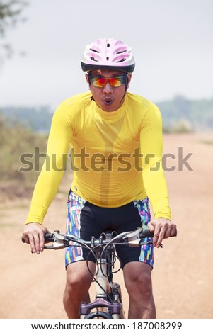 close up face of young man riding mountain bike in dusty road use for ...