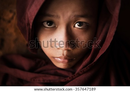 Close up face of  young novice monk covered with robe, low light with noise setting, Bagan, Myanmar. - stock photo