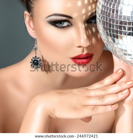 Close-up face of young woman with fashionable make-up and disco ball in hands - stock photo