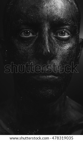 close-up face portrait  in flowing black paint in dark glitter