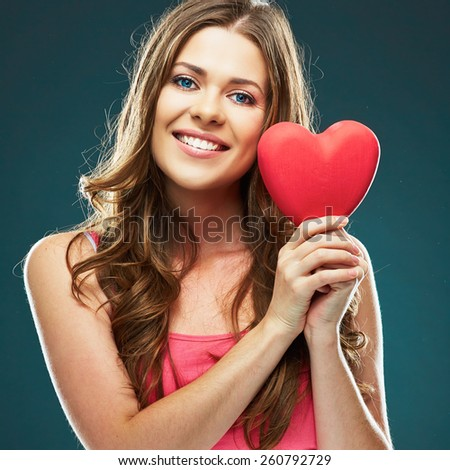 Close up face portrait of smiling woman holding red heart. Female model with long hair. - stock photo